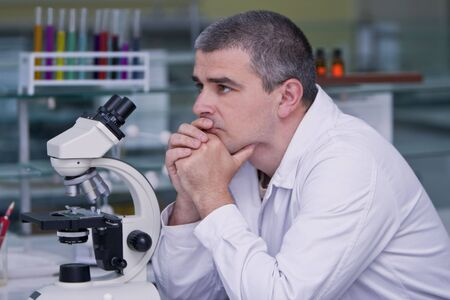 intent: Reasearcher thinking at his workplace in a laboratory.