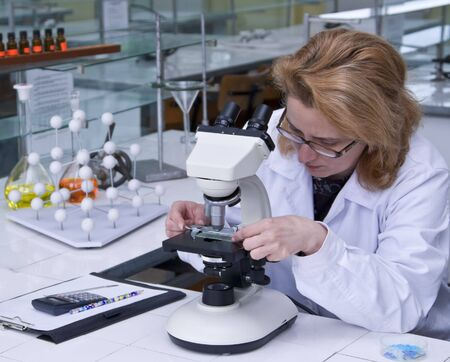 Female researcher fixing a spangle on a microscope. photo