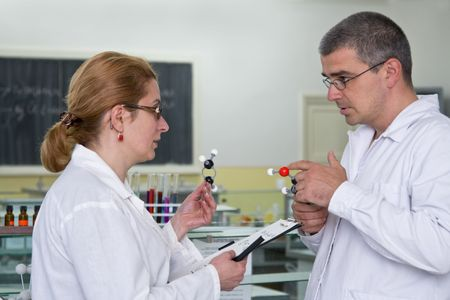 Two researchers discuss about the experiemnt strategy in a laboratory.All the inscripstions are mine. Stock Photo - 3219451