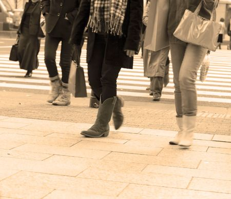 cross leg: Personas piernas para caminar en una ciudad de colores de tonos sepia.