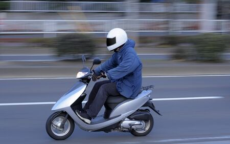 panning: Panning image of a man riding a scooter in a city.