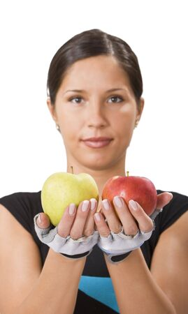 Young sportsgirl offering a red and a green apple and inviting people to a healthy diet.Selective focus on the apples. Stock Photo - 3246600