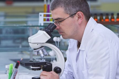 Male researcher looking through a microscope in a laboratory. Stock Photo - 3287706
