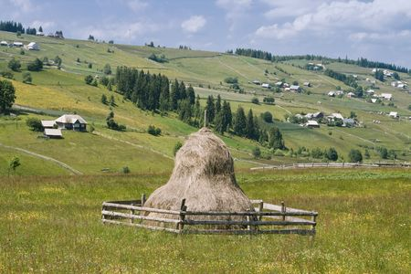 rick: Romanian mountain village with a hay rick in the central first plane. Location: The Apuseni Mountains, Transylvania.
