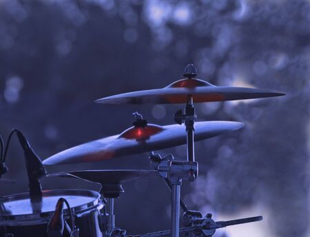 Image of cymblas and drum during a rock concert with specific lighting. photo