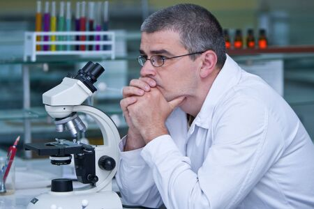 Reasearcher thinking at his workplace in a laboratory. photo