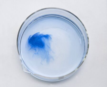 dissolution: Blue substance dissolving in a glass recipient-upper view. Stock Photo