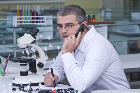 A male researcher using a mobile phone at his workplace in the laboratory.Al the inscriptions are mine. Stock Photo