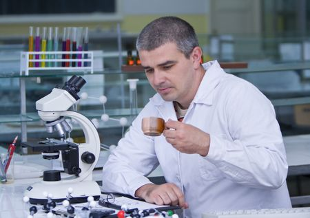 Researcher drinking a cup of coffee at his workplace in a laboratory. Stock Photo - 3357705