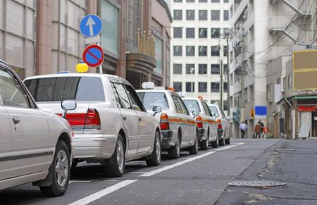 Row of some Japanese cabs in a small city street.