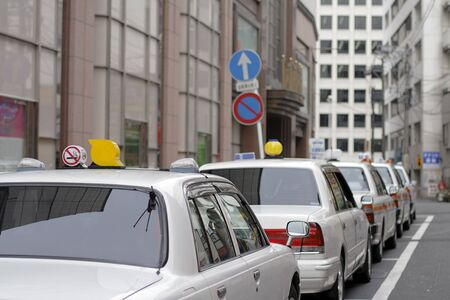 Japanese cabs in a row in a small crowded city street. Stock Photo - 3380620