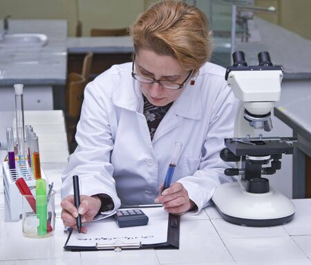Female researcher taking notices at her workplace.All inscriptions are mine. Stock Photo - 3425896