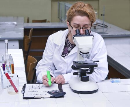 Female researcher taking notices while she is using a microscope.All inscriptions are mine. Stock Photo - 3446803