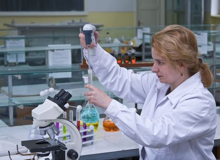 Image of a female researcher dropping a solution into a recipient in a laboratory. Stock Photo - 3471438
