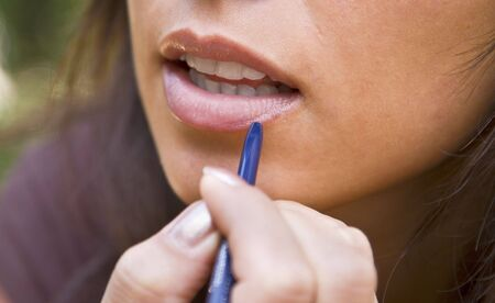Close-up image of a woman applying lipstick on her lips. Stock Photo - 3471439