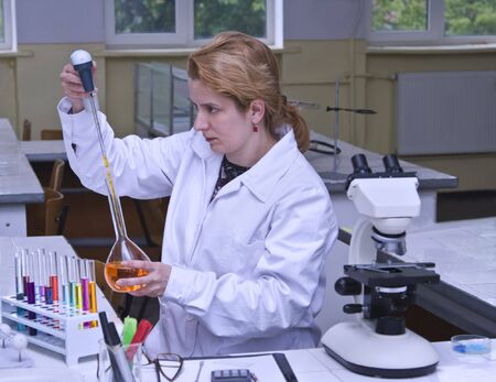 Image of a female researcher dropping a solution into a recipient in a laboratory. Stock Photo - 3471459
