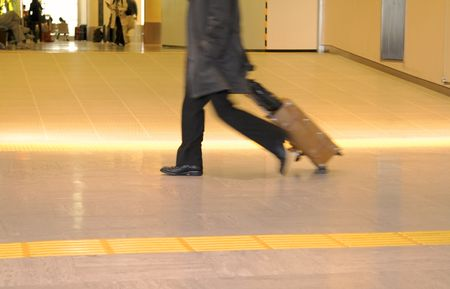 Motion blur image of a traveller carrying suitcase in an airport. Stock Photo - 3544915