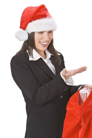 santaclause hat: Happy young woman in a red hat discovering gifts in Santas sack.You can put your product on her palm.