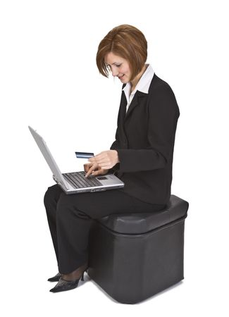 pouffe: Businesswoman sitting on a pouffe and buying something online using a credit card.