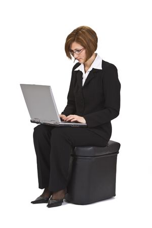 pouffe: Businesswoman sitting on a pouffe and working on a laptop.