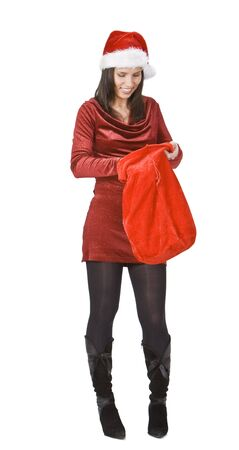 Young woman in red clothes and hat looking for the gifts in Santas sack. photo