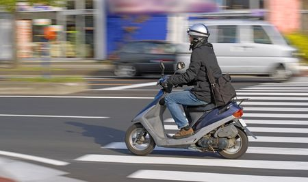 Image of a young man driving a scooter in a city photo