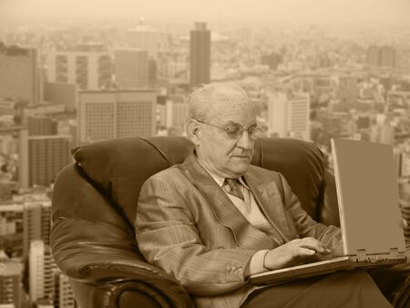 Senior businessman working on his laptop in front of the office window in a big city. The sepia colors accentuates the contrast between the mans age and the modern technology he is using. photo
