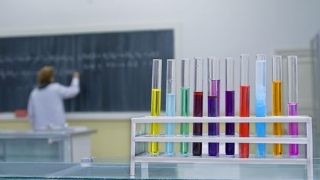 Image in a school chemiostry lab.Selective focus on the tubes in foreground.In the background there is a student writing someting on the blackboard. photo