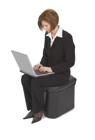 Businesswoman sitting on a pouffe and working on a laptop. photo