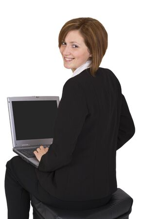 pouffe: Businesswoman sitting on a pouffe with a laptop in her lap and looking up back over the shoulder.