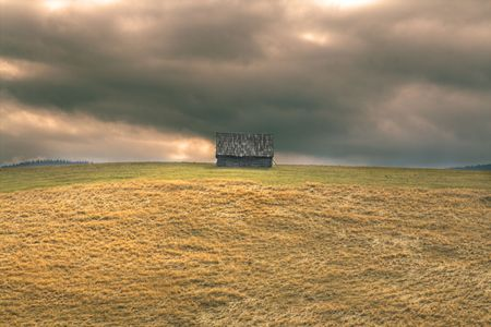 Lonely hut in a mountain area with a dramatic heavy sky.Location: Paltinis,Romania. Stock Photo - 3853627