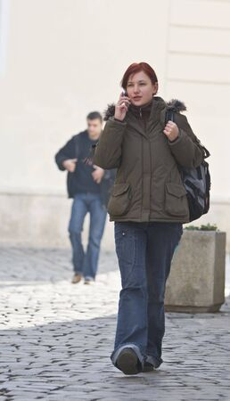 Redheaded girl student at the phone while is walking on a paved street. Stock Photo - 3859730