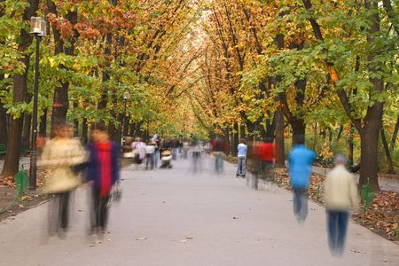 Blurred image of people walking in an autumn park. photo