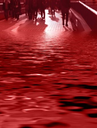 Abstract image of business people and their shadows walking on a pavement bridge partial covered in flood water-red tones photo