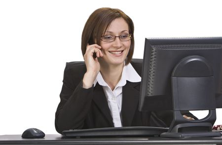 proffessional: Smiling businesswoman on a mobile phone at his place in the office. Stock Photo