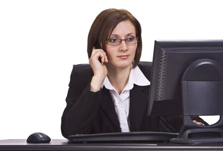 Serious businesswoman on a mobile phone looking to the monitor in the office. Stock Photo - 3895826