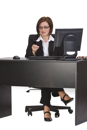 Businesswoman checking her mobile phone while siting on her desk. Stock Photo - 3895839