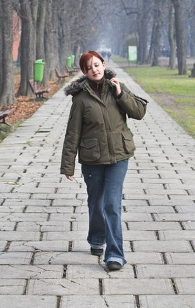 solely: Redheaded girl walking alone in an autumn park.
