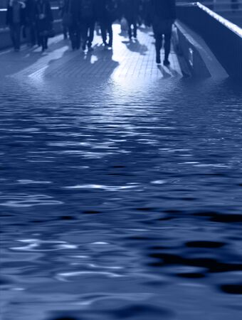 flee: Abstract image of business people and their shadows walking on a pavement bridge partial covered in flood water-red tones Stock Photo