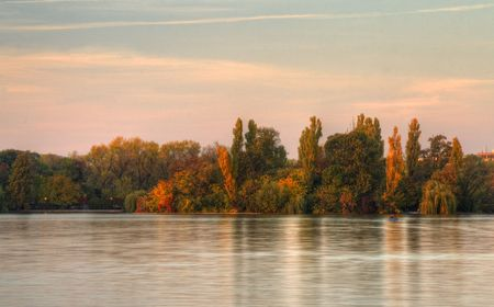 Beautiful forest reflected in the lake in a fall sunset.Location:Herastrau Lake,Bucharest,Romania. Stock Photo - 3959022