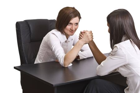 Businesswomen arm wrestling against a white background. photo