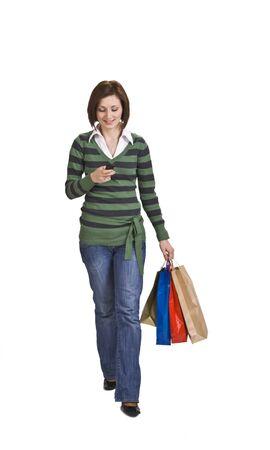 fiestas electronicas: Mujer con bolsas de la compra de cheques de su tel�fono m�vil. Foto de archivo