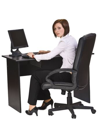 side job: Young businesswoman at her desk working on the computer and looking back over the shoulder.