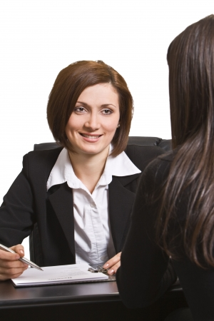 clarification: Two businesswomen at an interview in an office.The documents on the desk are mine. Stock Photo