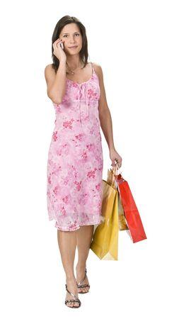 Mujer joven con bolsas de la compra utilizando un tel�fono m�vil. Foto de archivo - 4091611