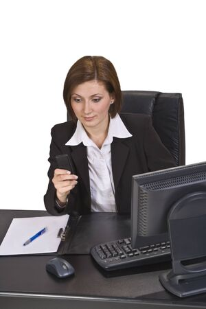 Businesswoman checking her mobile phone while siting on her desk. Stock Photo - 4145873