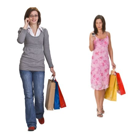 Two young women with shopping bags using a mobile phone. Stock Photo