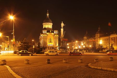 cluj: Night image of Avram Iancu square in Cluj Napoca,Romania.In the centre of the image,you can see the Orthodox Cathedral and Avram Iancus statue.At the periphery there are important administrative and religious buildings. Stock Photo