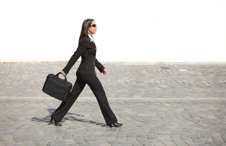 Young businesswoman walking along a cobbled street in front of a white wall. Stock Photo - 4871125