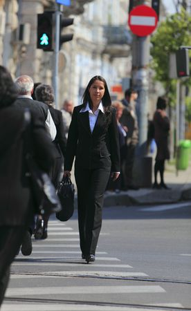 resolute: Young brunette businesswoman crossing the street in a city.